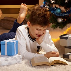 A boy reading a book under the christmas tree
