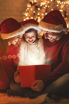 A small family opening a Christmas gift